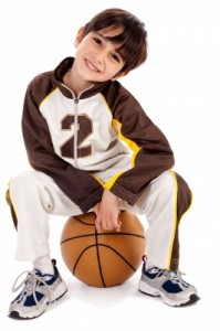 Cute Boy Sitting on a Basketball
